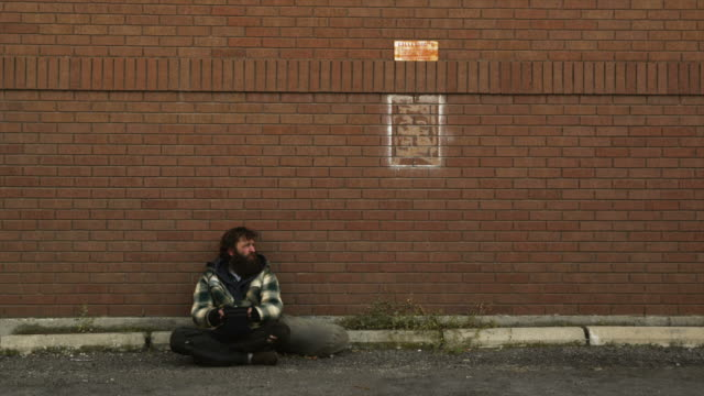 vídeos de stock, filmes e b-roll de ws man giving money to homeless man sitting on street, salt lake city, utah, usa - mendigo