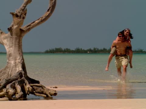 ms,  man giving piggy back ride to woman on beach,  harbour island,  bahamas - haarschmuck stock-videos und b-roll-filmmaterial