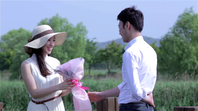 a man giving pink flower bouquet for the woman - south korea couple stock videos & royalty-free footage