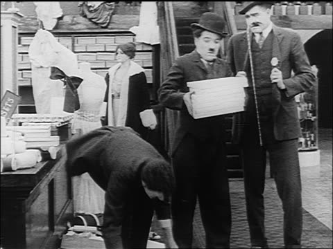 man giving stacks of thin boxes to charlie chaplin / chaplin dropping boxes - 1916 stock videos & royalty-free footage