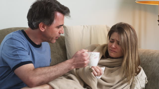 MS Man giving tea to coughing woman lying on sofa, Phoenix, Arizona, USA