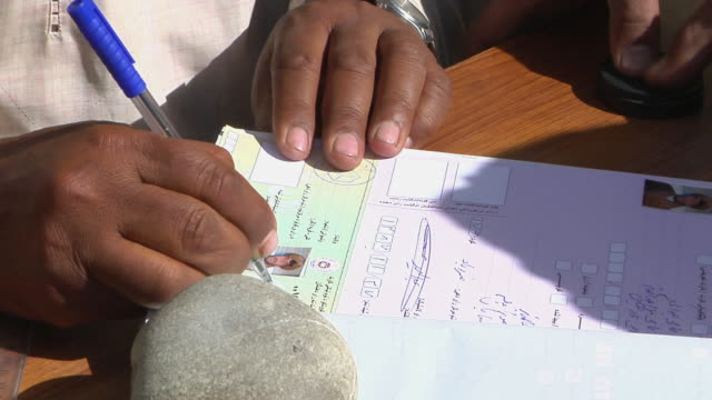 man giving thumb print on election form / musa qala, helmand province, afghanistan. - 2009 stock-videos und b-roll-filmmaterial