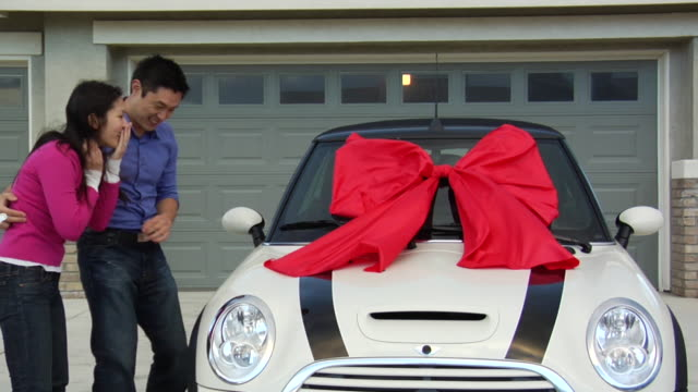 vidéos et rushes de ms man giving woman new sports car with red bow as surprise gift / los angeles, california, usa - noeud à boucle