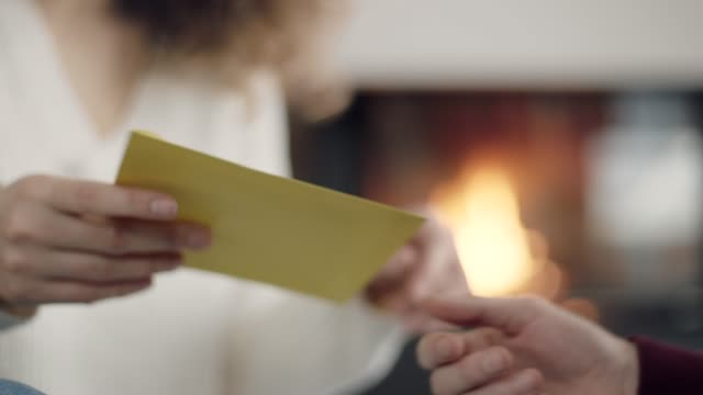 Man giving yellow envelope to woman