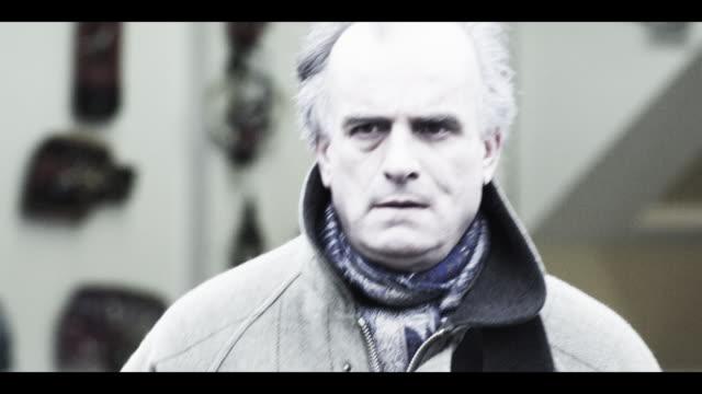 a man glances around as he walks through a crowd. - sideways glance stock videos & royalty-free footage