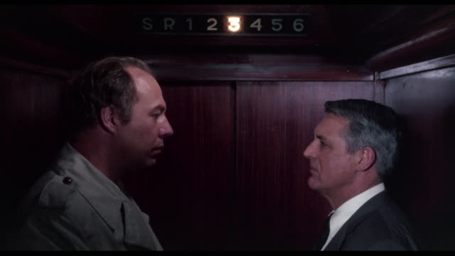 1963 man (cary grant) glares at another man (george kennedy) as they ride the elevator - embarrassment stock videos & royalty-free footage