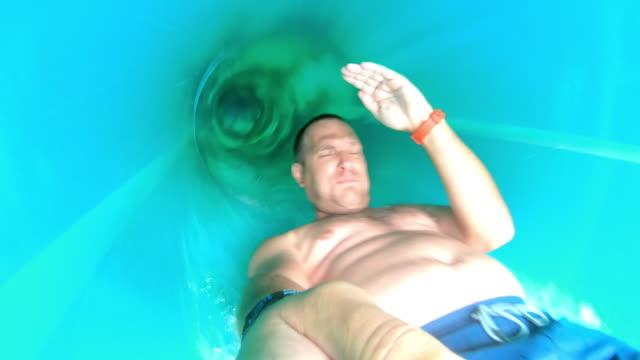 vídeos de stock e filmes b-roll de pov man gliding down the water slide - escorrega de água