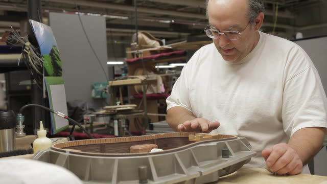 MS Man gluing interior of guitar shell / Nazareth, Pennsylvania, USA