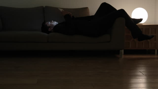 man goes and lies down on a couch with his wireless touch screen device and then lets it be - electric lamp stock videos and b-roll footage