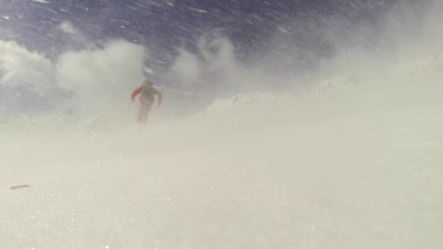 a man goes cross-country skiing on a very windy day. - slow motion - ウィンターコート点の映像素材/bロール