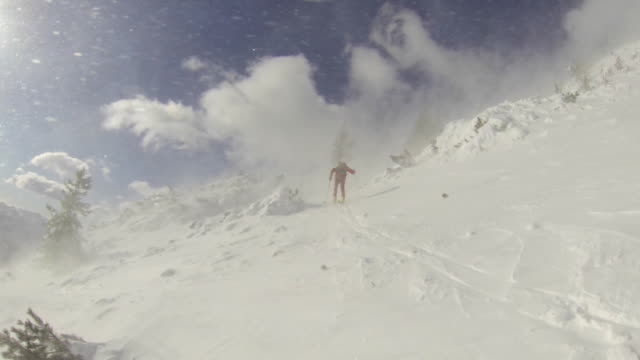 A man goes cross-country skiing on a very windy day. - Slow Motion