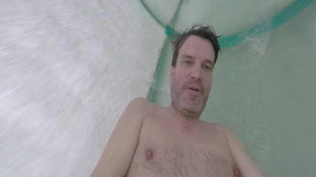 man goes down a water slide