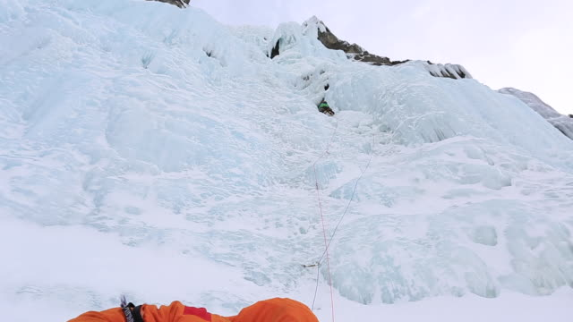 A man goes ice climbing on a mountain in the winter.