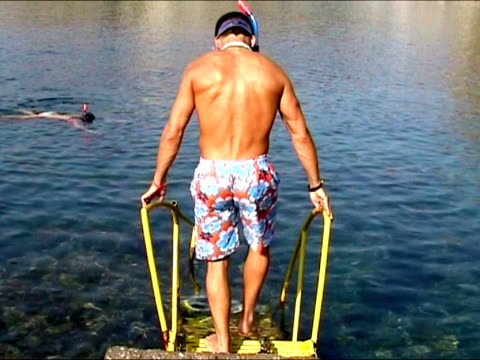 stockvideo's en b-roll-footage met man going into the water to do some snorkeling - zwembroek