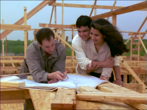 man going over blueprints with excited couple at construction site - femmina con gruppo di maschi video stock e b–roll