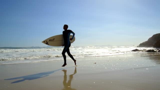 man geht entlang einer atemberaubenden küste surfen - kapstadt stock-videos und b-roll-filmmaterial