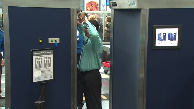 Man Going Through Airport XRay Scanner at Chicago O'Hare Airport on December 13 2013 in Chicago Illinois