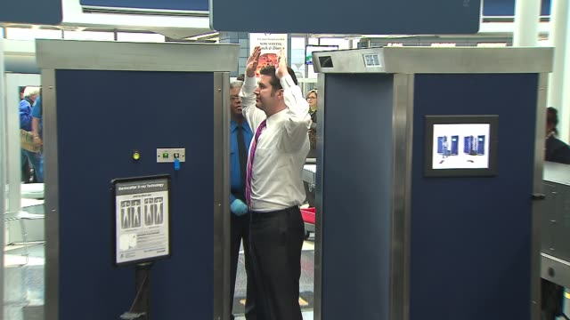 WGN Man Going Through Airport XRay Scanner at Chicago O'Hare Airport on December 13 2013 in Chicago Illinois
