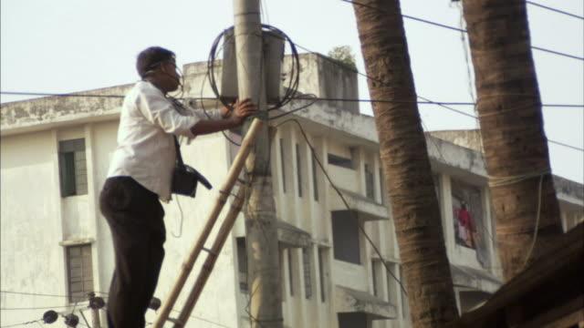 MS, TU, TD, Man going up ladder adjusting box on electricity pole, Dhaka, Bangladesh
