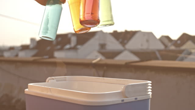 Man grabbing cold drink from a cooler during rooftop party