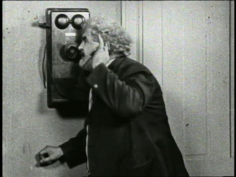 b/w 1926 man (jim donnelly) grabbing phone from other man + starts yelling / rips phone off wall - 精神障害点の映像素材/bロール