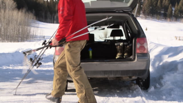 man grabbing ski poles and skis and walking away from car / ketchum, idaho, united states - sports equipment stock videos & royalty-free footage