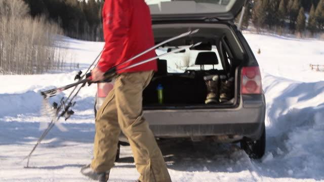 man grabbing ski poles and skis and walking away from car / ketchum, idaho, united states - attrezzatura sportiva video stock e b–roll