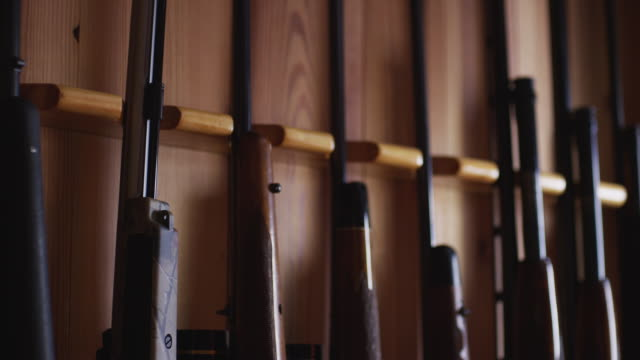man grabs a rifle from a rack filled with various weapons, firearms and guns. - ライフル点の映像素材/bロール