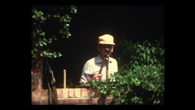 1982 man grabs clippers and heads for his garden - home movie stock videos & royalty-free footage