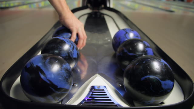vídeos de stock, filmes e b-roll de man grabs duckpin bowling ball and throws it - sapato de boliche