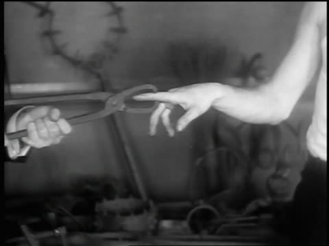 vidéos et rushes de b/w 1932 ms man grasping pointer finger of another man with metal tongs / torture instruments in background - pincer