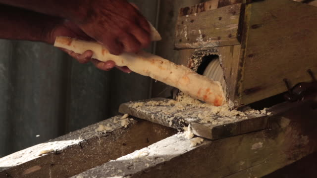 Man gratting manioc at old machine - manioc flour (two sequence images)
