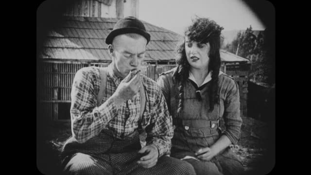 1916 man (al st. john) greedily eats peach in front of woman (mabel normand) - 1916 stock videos & royalty-free footage