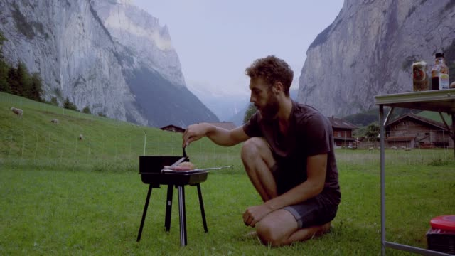 man grilling burger in camping in swiss alps - preparing food stock videos & royalty-free footage