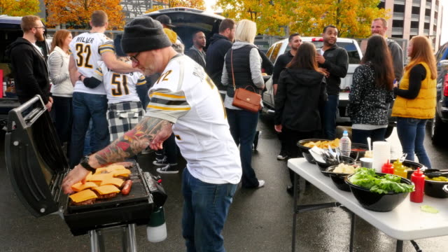 MS Man grilling burgers and hot dogs at portable barbecue during tailgating party in stadium parking lot
