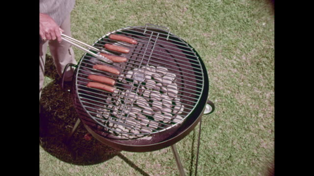 vídeos de stock e filmes b-roll de ms ha man grilling sausages on barbecue grill / united states - salsicha