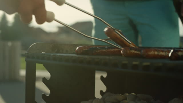 stockvideo's en b-roll-footage met een man grills hotdogs - picknick