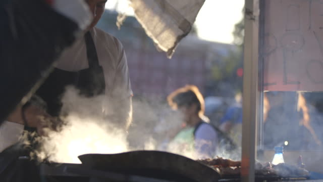 Man grills meat on Santiago street, medium shot