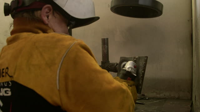 man grinds metal in workshop - respiratory equipment stock videos & royalty-free footage