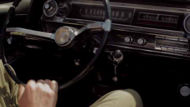 a man grips the steering wheel of a vintage convertible as his hair blows in the wind. - 点火装置点の映像素材/bロール