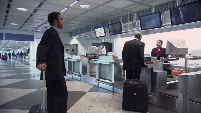 ms pan man growing impatient while waiting in line at airport check-in counter/ munich, germany - airline check in attendant stock videos and b-roll footage