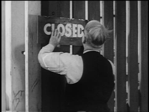 "stockvideo's en b-roll-footage met man hammering ""closed"" sign on gate of factory during great depression - 1936"
