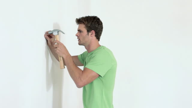 Man hammering nail into wall and woman hanging picture