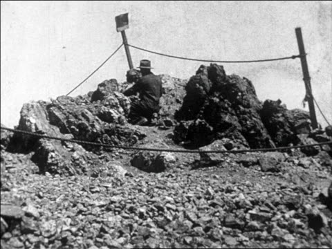 B/W 1927 man hammering on rocks looking for gold / Nevada / newsreel