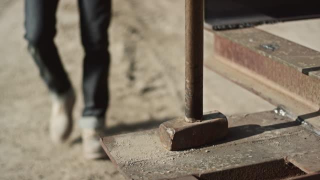 Man hammering outside