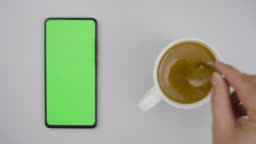 Man Hand Cup of Hot Coffee and Using Smartphone Watching Green Screen Top View. Smartphone with Green Mock-up Screen Business Concept. Person Hand Stirring Coffee with Spoon on Table. Slow Motion.