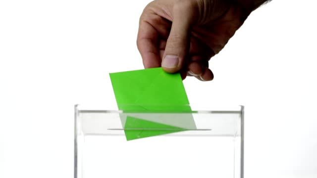 man hand dropping green envelope into voting ballot to support environmental conservation - ballot box stock videos & royalty-free footage