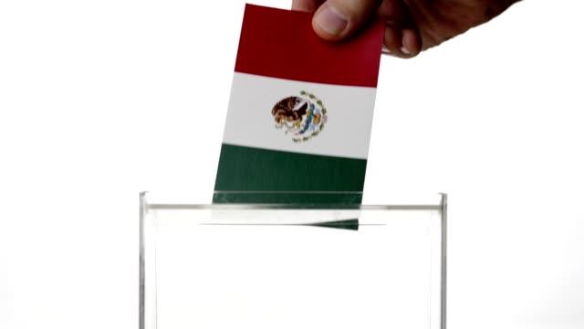 vídeos de stock, filmes e b-roll de mão do homem que deixa cair a bandeira mexicana na cédula de votação - méxico