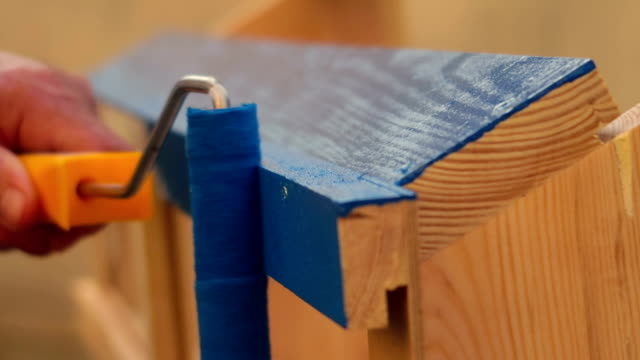 Man hand hold paint roller and paint / renovate a wooden furniture in blue at home, close-up.
