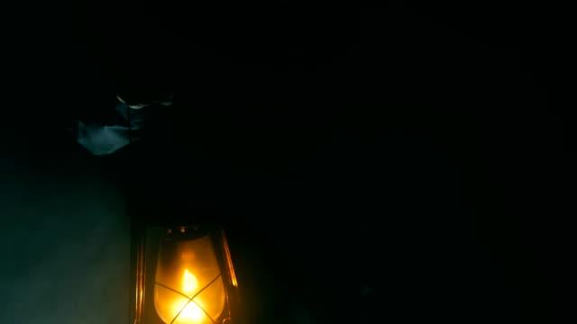 vidéos et rushes de main d'homme tenant une lampe à pétrole dans la nuit - lampe électrique